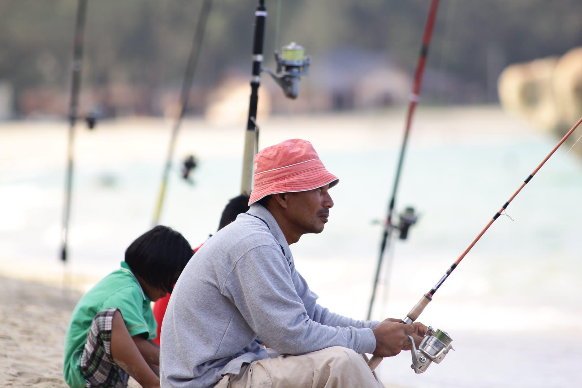 man sitting on edge fishing on river